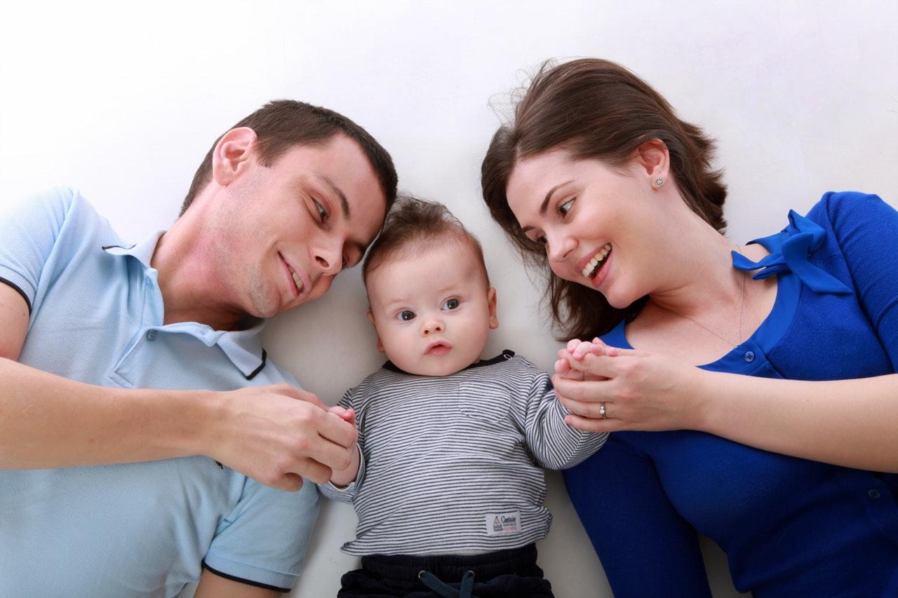 Zdjęcie przedstawia uśmiechniętą rodzinę. Leży kobieta, dziecko i mężczyzna.. Dorośli trzymają dziecko za ręce.